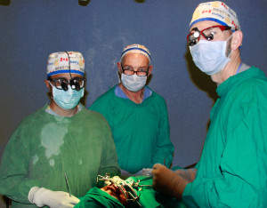 Dr. Cliff Moore (centre) scrubbed in assisting surgeons Dr. Adil Ladak (left) and Dr. Stan Valnicek.