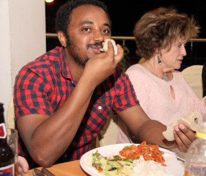 Rotaract Club President Yohannes demonstrates the fine art of eating with native Ethiopian Indira
